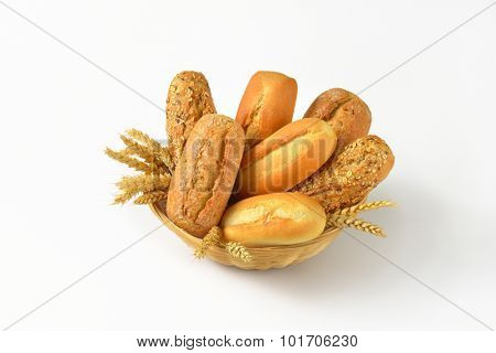 basket of various bread rolls and buns on white background poster