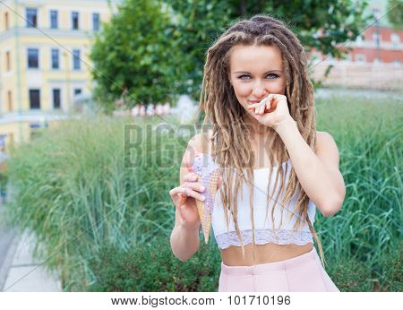 Young sexy blonde girl with dreads eating multicolored ice cream in waffle cones in summer evening,