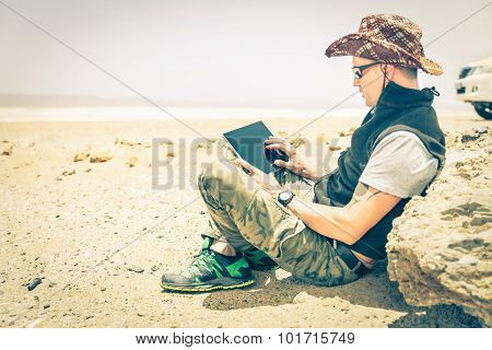 Young Hipster Man Sitting In Desert Road - Concept Of Modern Technologies With Alternative Travel