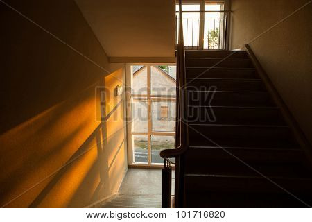 Staircase Of Apartment Building With Sunset Light Playing On The Wall