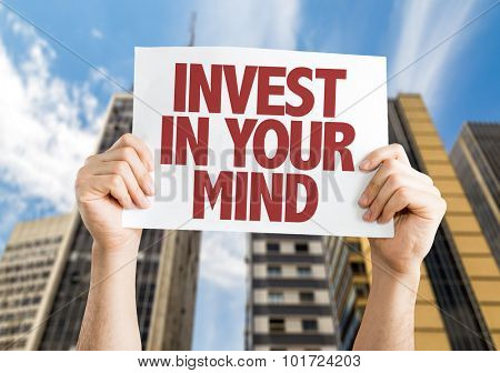 Invest In Your Mind placard with cityscape background