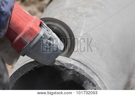 Plumbers cutting concrete water pipes by metal grinding poster