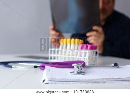 Medical doctor  sitting at table and looking patients roentgen