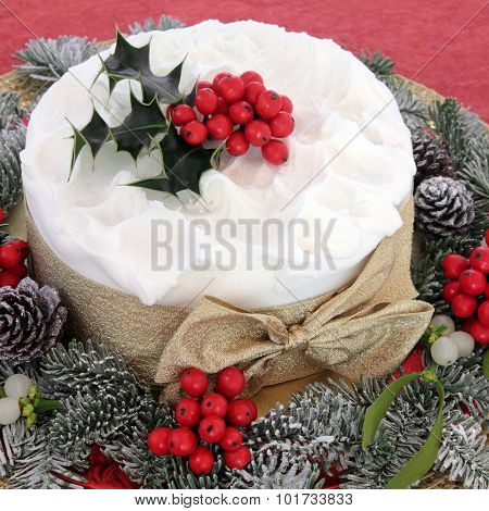 Christmas cake with holly, mistletoe and winter greenery over red background. poster