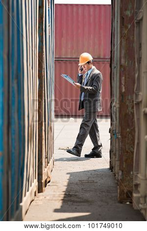 Vertical image of a busy port inspector calling by phone and working with his plan on the foreground. poster