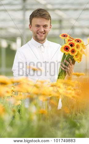 Young man working in a greenhouse full of flowers.