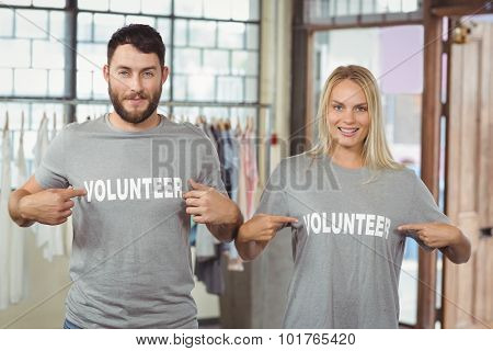 Man and woman showing volunteer text on tshirts in office
