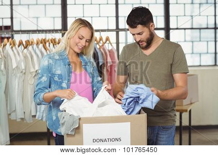 Volunteers looking at clothes in donation box in creative office
