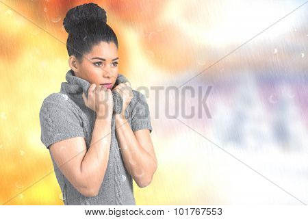 Pretty girl in winter jumper shivering against autumn changing to winter