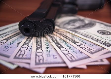 Gun, drugs and money on wooden background