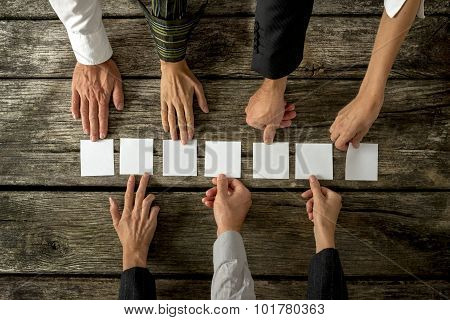 Seven Hands Of Business People  Placing Seven White Cards In A Row