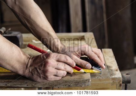 Carpenter Taking Measurement Of A Wooden Plank
