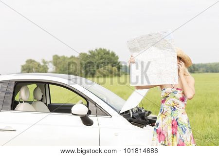 Woman using cell phone while reading map by broken down car at countryside