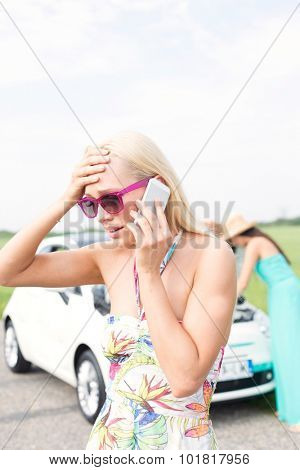 Frustrated woman using cell phone while friend examining broken down car at countryside