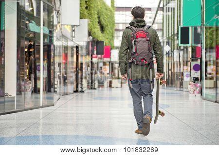 Young man, carrying a skateboard, walking casually through a modern shopping mall.