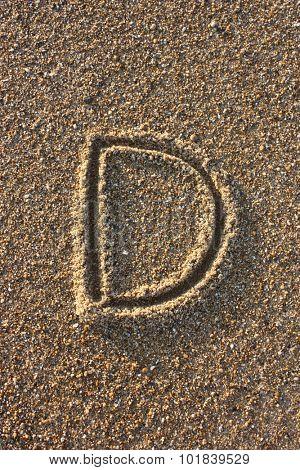 Alphabet's letter D handwritten in sand on the beach, at sunrise.