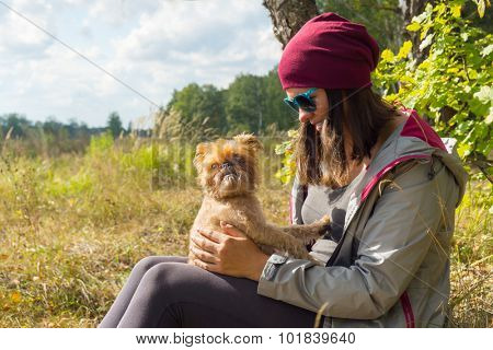 Young woman plays with small dog Griffon Bruxellois breed outdoors