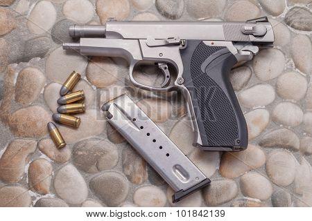 Use Modern handgun M9 close-up.on a rock background. poster