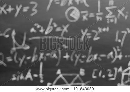 Blurred maths formulas written by white chalk on the blackboard background. poster