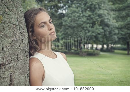 sad young woman leaning against tree retro style