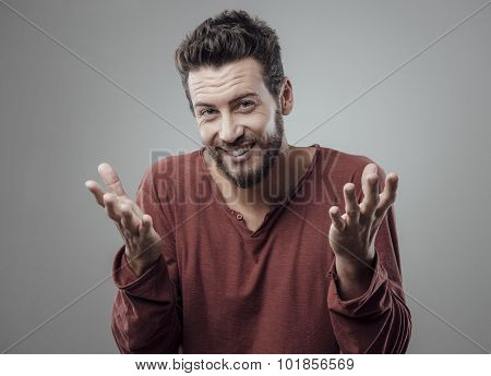 Confused young man shrugging and smiling at camera poster