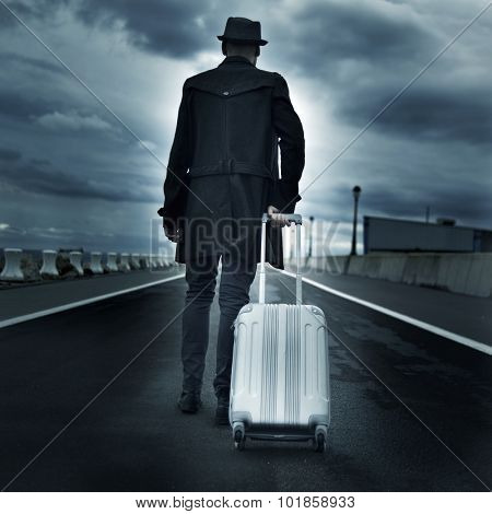 closeup of a young man seen from behind carrying his rolling suitcase, with a dramatic effect