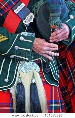 Bagpipe player plays music with Great Highland Bagpipe.