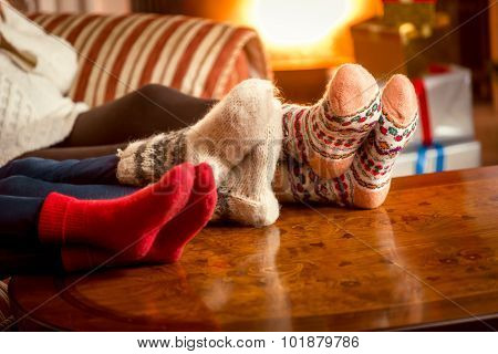 Closeup Conceptual Shot Of Family Warming Feet At Fireplace