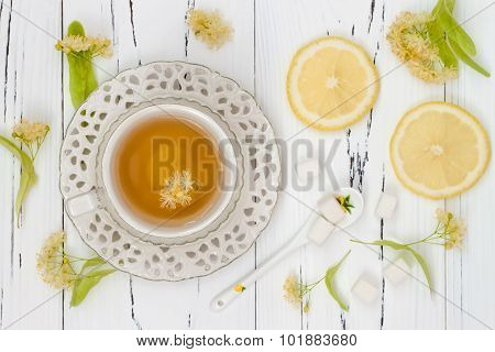 Cup of herbal tea with linden flowers lemon and honey on a old wooden background. Top view