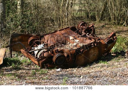Upside down rusting car in a wood