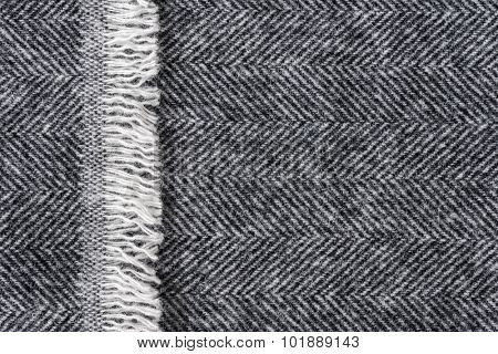 Herringbone wool tweed fabric background with closeup on textile texture and overlapping fringe edge poster