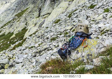 Rope, Helmet, Carabiners, Climbing Harness And Descender On The Rock