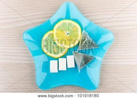 Tea Bags, Slices Of Lemon And Lumpy Sugar In Plate