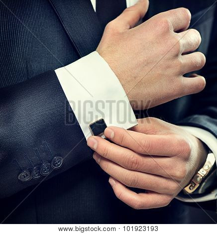 Close up of businessman wearing cufflinks. Elegant young fashion business man wearing suit