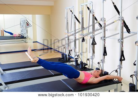 Pilates reformer woman long spine exercise workout at gym indoor