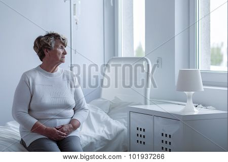 Ill lonely woman sitting on hospital bed poster