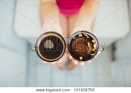 Women's hands holding tea and coffee
