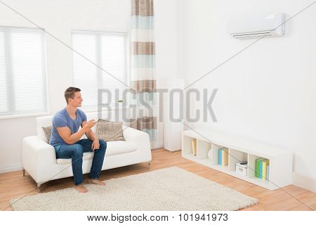 Young Man Operating Air Conditioner