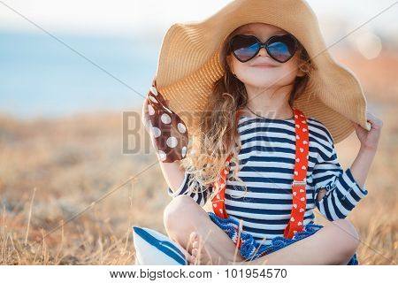 The happy little girl in a big hat