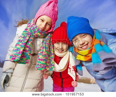 Joyful kids in winterwear looking at camera in natural environment