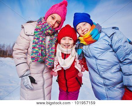 Joyful kids in winterwear looking at camera outdoors