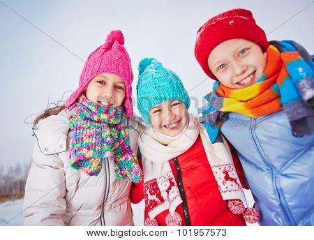 Joyful friends in winterwear looking at camera outdoors