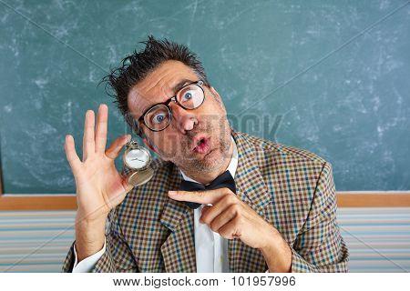 Nerd silly teacher showing vintage chain watch in green blackboard