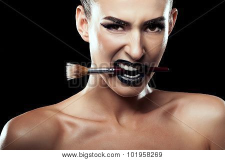 Woman With Make Up Brush In Mouth On Black Background