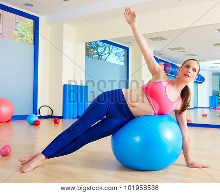 Pilates woman side bend fitball exercise workout at gym indoor swiss ball poster