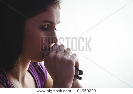 Woman praying with wooden rosary beads on white background