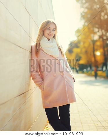 Beautiful Young Smiling Woman Wearing A Pink Coat In Sunny Autumn City