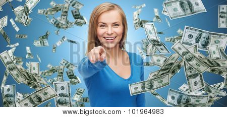 business, money, finance, people and gesture concept - smiling woman with dollar cash money pointing finger on you over blue background