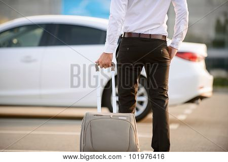 Nice businessman holding suitcase