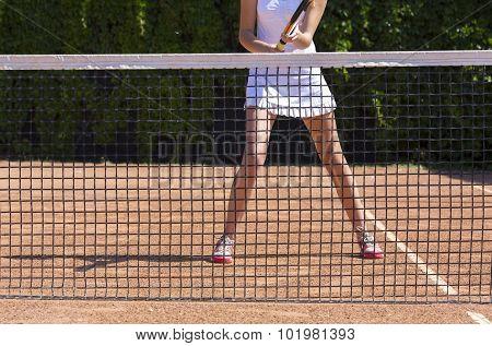 Slim legs of female tennis athlete behind fishnet barrier